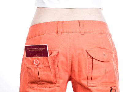 authorities: Back view of female buttocks in orange pants with russian passport in pocket.