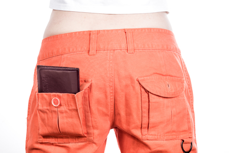 naturalization: Back view of female buttocks in orange pants with russian passport in pocket.