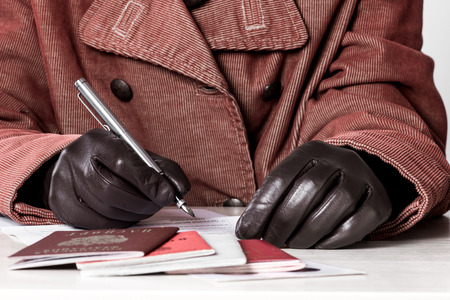 naturalization: Female hands in gloves filling the document forms at the table. Stock Photo