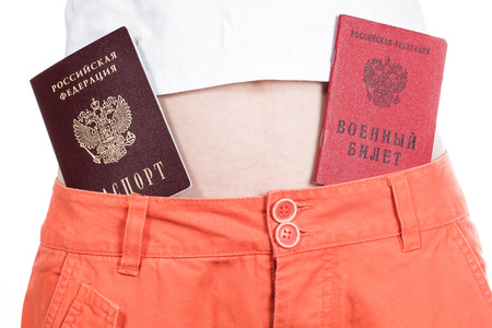 authorities: Front view of female hips in orange pants with russian passport and military ID in belt.