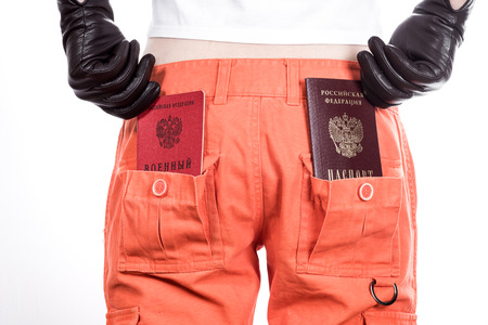 naturalization: Back view of female buttocks in orange pants with russian passport and military ID in pockets.