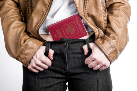 naturalization: Front view of female hips in breeches with  white T-shirt and jacket and russian passport in belt. Stock Photo