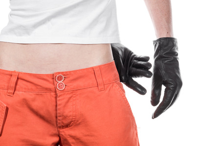 pickpocket: Front view of female hips in orange pants with  white T-shirt and gloved hands.