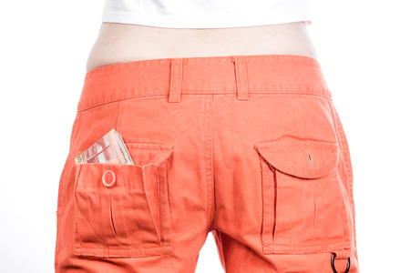 inattention: Back view of female buttocks in orange pants with money in pocket.
