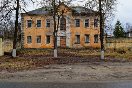 desolation: Abandoned three-storey building in peach color with trees in the foreground. Concept of neglection and desolation. Stock Photo