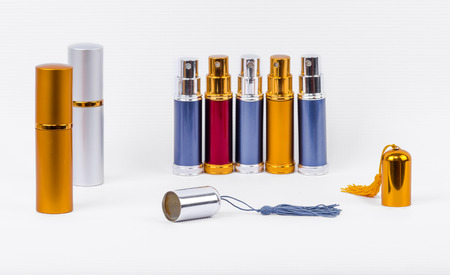 ranked: Metal perfume atomizers of the same cylindrical shape ranked. Cap with a brush in front of them. Isolated image on white background. Stock Photo