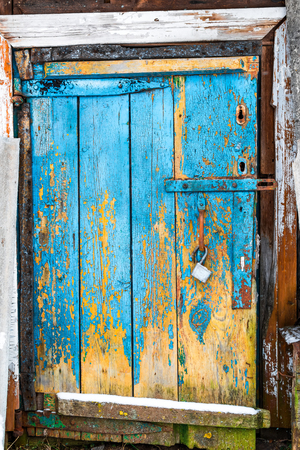 outbuilding: Old rough door in the wooden wall of outbuilding.