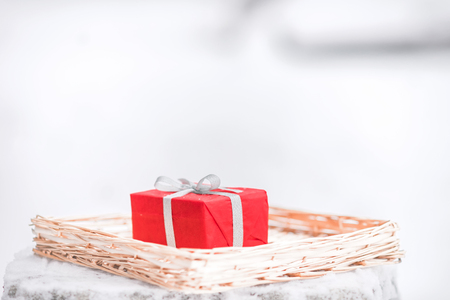 silver ribbon: Red gift box with silver ribbon on straw tray on the snow background. Closeup picture. Stock Photo