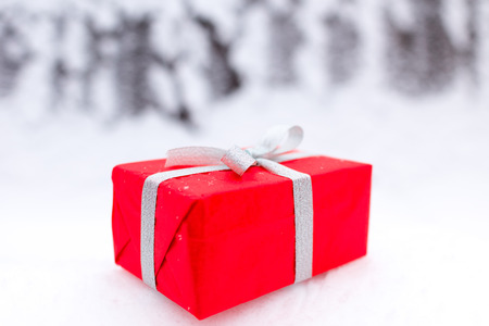red gift box: Red gift box with silver ribbon on the snow background. Closeup picture.