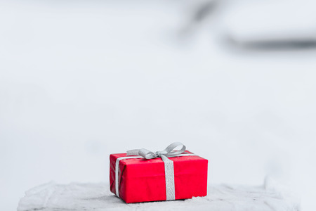 silver ribbon: Red gift box with silver ribbon on the snow background. Closeup picture.