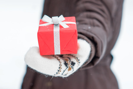 gifting: Hand in a wool mitten holding red gift box on snow background. Closeup picture.