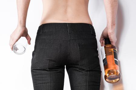 silhouette femme: main Femme tenant une bouteille de whisky et de verre près des hanches. L'image de la partie de la figure féminine. Concept de la consommation d'alcool.