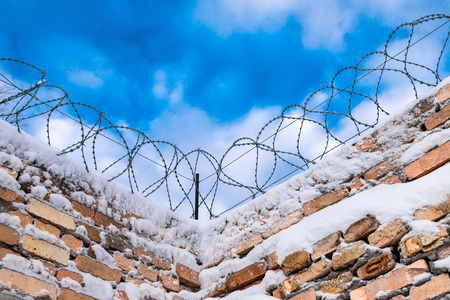 barblock: Closeup of brick fence with barbered wire on the sky background. Stock Photo