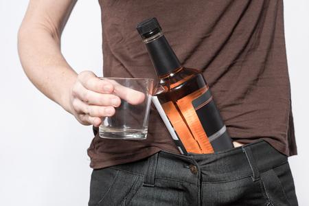 silhouette femme: main Femme tenant une bouteille de whisky et un verre pr�s de la taille. L'image de la partie de la figure f�minine. Concept de la consommation d'alcool.