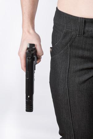 silhouette femme: main Femme tenant un fusil près des hanches. L'image de la partie de la figure féminine. Concept de danger.