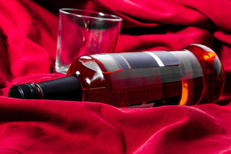 intoxicating: Bottle of whiskey and a glass lying on a red drapery. Close-up shot. Concept of luxury.