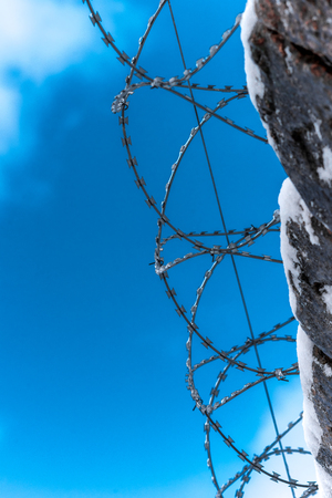 gaol: Closeup of brick fence with barbered wire on the sky background. Stock Photo
