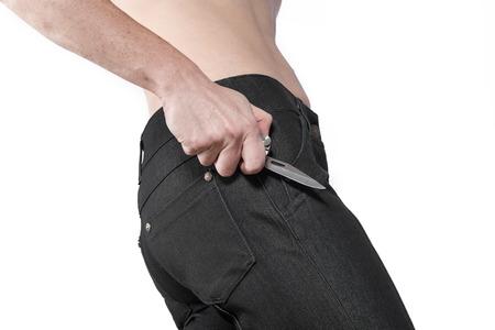 delito: Mano femenina que sostiene un cuchillo cerca de su cadera. La imagen lateral de la parte de la figura femenina. Concepto de peligro y delito.