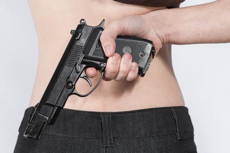 delito: Mano femenina que sostiene una pistola detr�s de la espalda. La imagen de la parte de figura femenina. Concepto de peligro y delito. Foto de archivo