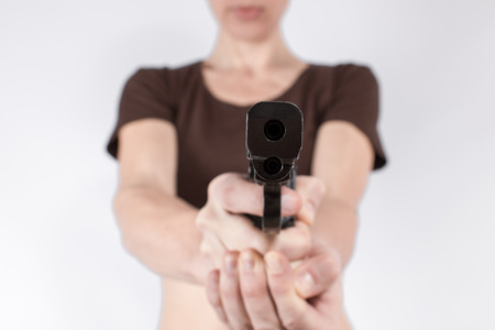 female assassin: Female hands aiming a gun in the direction of a viewer.