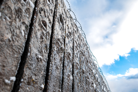barblock: Closeup of concrete fence with barbered wire on the sky background. Stock Photo