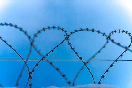 barblock: Closeup of barbered wire curls on the sky background.
