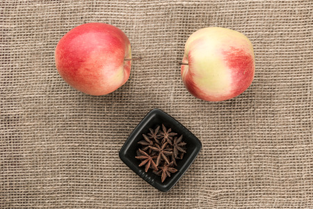 badiane: Composition of red apples and star anise on sackcloth background. Top view. Stock Photo