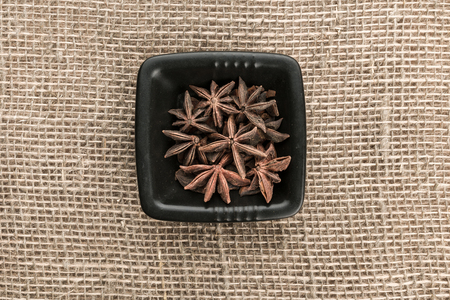 badiane: Little ceramic saucer of star anise on sackcloth background. Top view.
