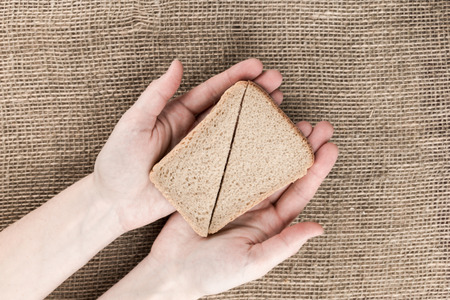 brown bread: Triangles of brown bread in female hands on sackcloth background. Top view. Stock Photo
