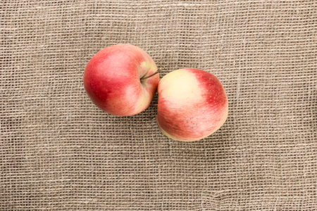 two on top: Two red apples lying on sackcloth background. Top view.
