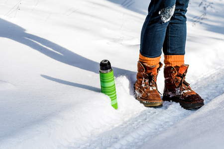 snow road: Feet in rusty boots and green thermos on the  snow road.
