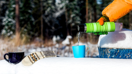 thermos: Female hand pouring water from thermos to the cup on a snowy bench on the edge of winter forest.