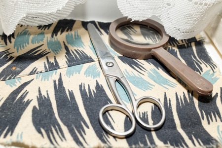 clothed: Scissors and a magnifying glass on the clothed windowsill.