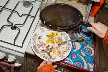 fried eggs: Hand holding a frying pan over the plate with fried eggs standing on the table.