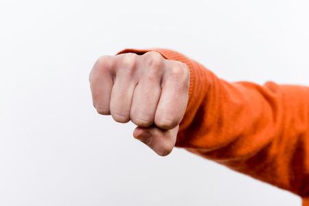 brawl: Female fist raised to strike. Front view.