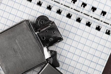 cigarette lighter: Middle of checked spiral notepad and cigarette lighter. Top view. Stock Photo