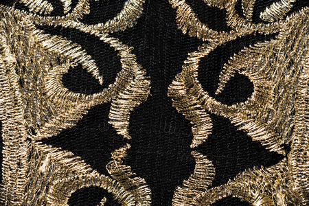 textural: Textural image. Fragment of vintage golden embroidery on black fabric.