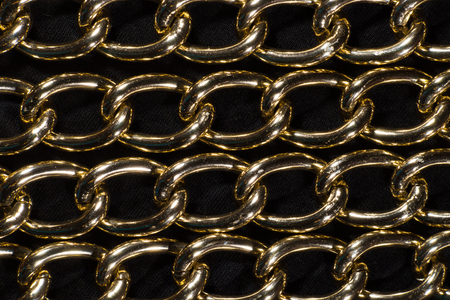 padding: Textural image. Several rows of large chains in yellow metal on a black background.
