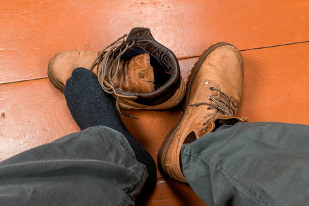 pies masculinos: Male feet in winter boots on the floor. First-person view.