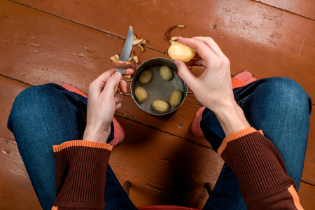 paring knife: Female hands peeling potato above painted wooden floor. First-person view.