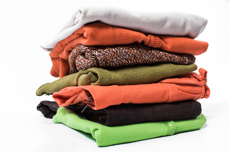 garments: Stack of folded garments. Closeup over white background. Stock Photo