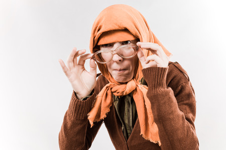 travesty: Grotesque grandmother character wearing big glasses and babushka on white background.