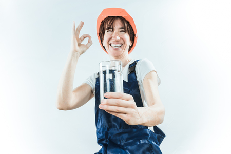 travesty: Worker wearing orange helmet holding glass of water on white background. Stock Photo