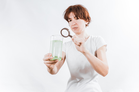 dubious: Woman holding a glass of strange green liquid. Concept of aquatic contamination. Stock Photo