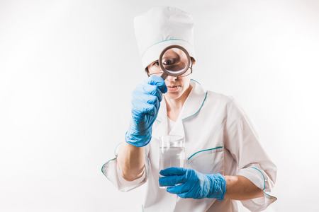travesty: Female doctor looking through magnifier on white background. Stock Photo