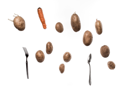 levitation: Brown potato tubers, carrot, spoon and fork flying in the air. Isolated image on white background. Stock Photo