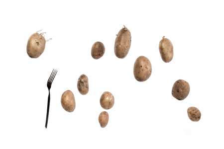 starvation: Brown potato tubers and fork flying in the air. Isolated image on white background.