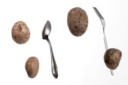 starvation: Brown potato tubers, spoon and fork flying in the air. Isolated image on white background.
