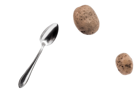 uncooked: Brown potato tubers and spoon flying in the air. Isolated image on white background.