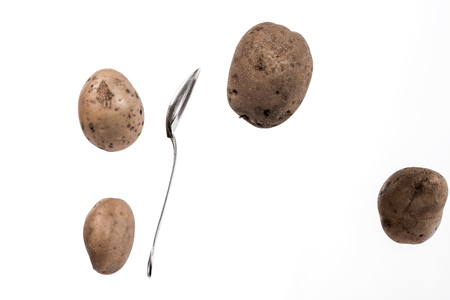 tuber: Brown potato tubers and spoon flying in the air. Isolated image on white background.